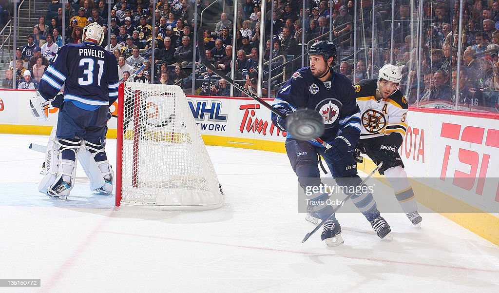 <a gi-track='captionPersonalityLinkClicked' href=/galleries/search?phrase=Zach+Bogosian&family=editorial&specificpeople=4195061 ng-click='$event.stopPropagation()'>Zach Bogosian</a> #4 of the Winnipeg Jets clears the puck around the glass as <a gi-track='captionPersonalityLinkClicked' href=/galleries/search?phrase=Patrice+Bergeron&family=editorial&specificpeople=204162 ng-click='$event.stopPropagation()'>Patrice Bergeron</a> #37 of the Boston Bruins skates after it during third period action at the MTS Centre on December 6, 2011 in Winnipeg, Manitoba, Canada.