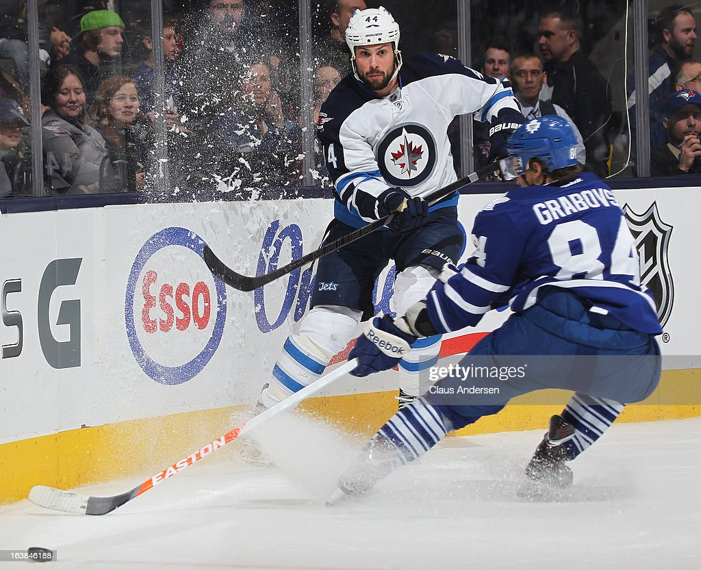 <a gi-track='captionPersonalityLinkClicked' href=/galleries/search?phrase=Zach+Bogosian&family=editorial&specificpeople=4195061 ng-click='$event.stopPropagation()'>Zach Bogosian</a> #44 of the Winnipeg Jets clears the puck away from <a gi-track='captionPersonalityLinkClicked' href=/galleries/search?phrase=Mikhail+Grabovski&family=editorial&specificpeople=2560547 ng-click='$event.stopPropagation()'>Mikhail Grabovski</a> #84 of the Toronto Maple Leafs in a game on March 16, 2013 at the Air Canada Centre in Toronto, Ontario, Canada. The Jets defeated the Leafs 5-4 in an overtime shoot-out.