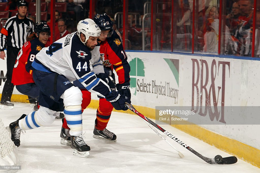 Zach Bogosian #44 of the Winnipeg Jets digs the puck out from the boards against Jonathan Huberdeau #11 of the Florida Panthers at the BB&T Center on March 5, 2013 in Sunrise, Florida.