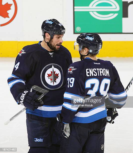 Zach Bogosian of the Winnipeg Jets discusses strategy with teammate Tobias Enstrom during a second period stoppage in play against the Nashville...