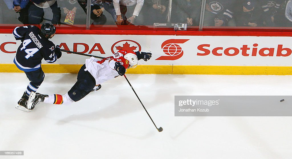 <a gi-track='captionPersonalityLinkClicked' href=/galleries/search?phrase=Zach+Bogosian&family=editorial&specificpeople=4195061 ng-click='$event.stopPropagation()'>Zach Bogosian</a> #44 of the Winnipeg Jets hooks up Shawn Matthias #18 of the Florida Panthers as they chase the loose puck along the boards during second period action at the MTS Centre on April 11, 2013 in Winnipeg, Manitoba, Canada.