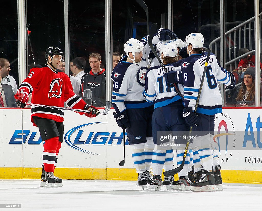 Zach Bogosian #44 of the Winnipeg Jets is congratulated by his teammates after scoring a first-period goal as Andy Greene #6 of the New Jersey Devils skates away during the game at the Prudential Center on February 24, 2013 in Newark, New Jersey.