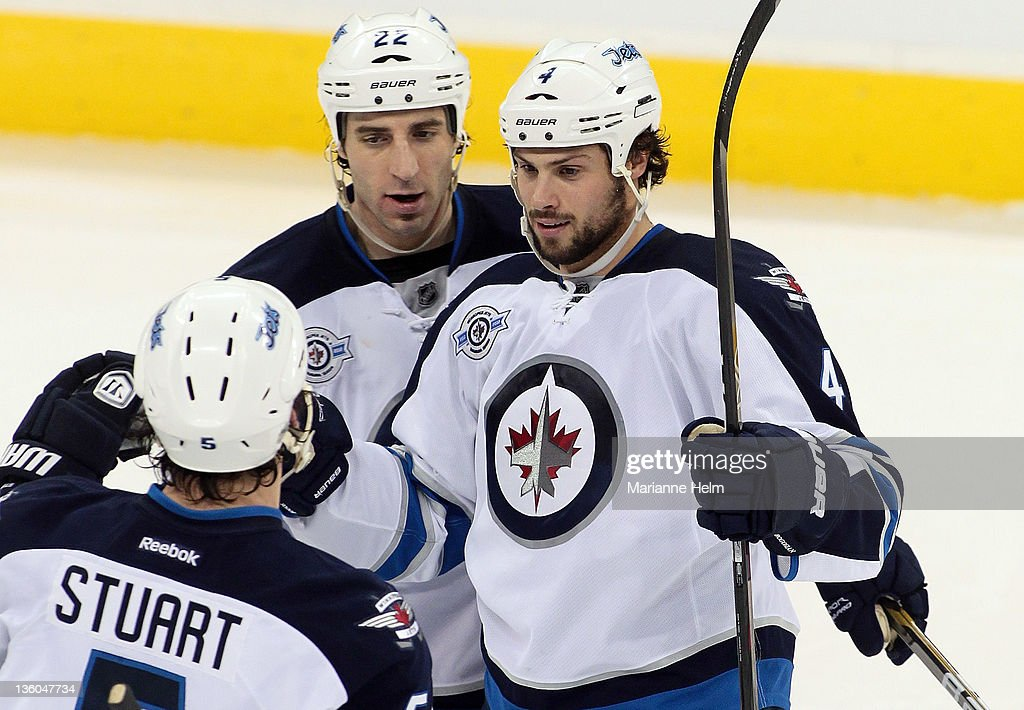 <a gi-track='captionPersonalityLinkClicked' href=/galleries/search?phrase=Zach+Bogosian&family=editorial&specificpeople=4195061 ng-click='$event.stopPropagation()'>Zach Bogosian</a> #4 of the Winnipeg Jets is congratulated by teammates <a gi-track='captionPersonalityLinkClicked' href=/galleries/search?phrase=Chris+Thorburn&family=editorial&specificpeople=2222066 ng-click='$event.stopPropagation()'>Chris Thorburn</a> #22 and Mark Stuart #5 after his goal against the Anaheim Ducks in NHL action at the MTS Centre on December 17, 2011 in Winnipeg, Manitoba, Canada.