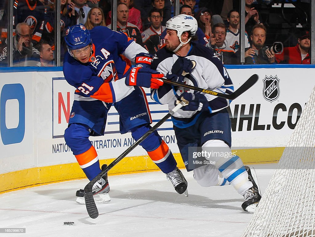 Zach Bogosian #44 of the Winnipeg Jets is held off by Kyle Okposo #21 of the New York Islanders at Nassau Veterans Memorial Coliseum on April 2, 2013 in Uniondale, New York. The Islanders defeated the Jets 5-2.