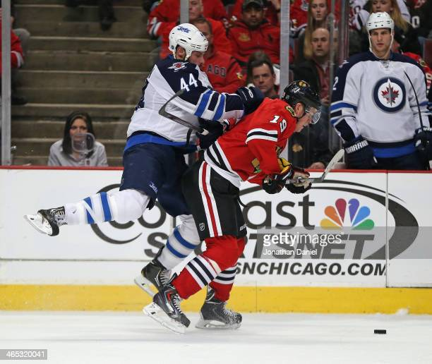 Zach Bogosian of the Winnipeg Jets jumps on the back of Jonathan Toews of the Chicago Blackhawks at the United Center on January 26 2014 in Chicago...