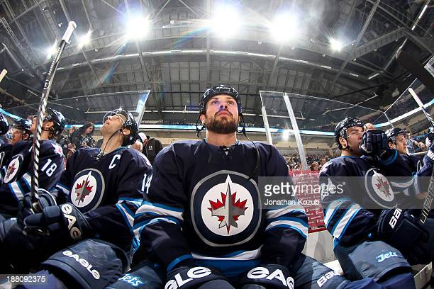 Zach Bogosian of the Winnipeg Jets looks on from the bench prior to puck drop against the Nashville Predators at the MTS Centre on November 8 2013 in...