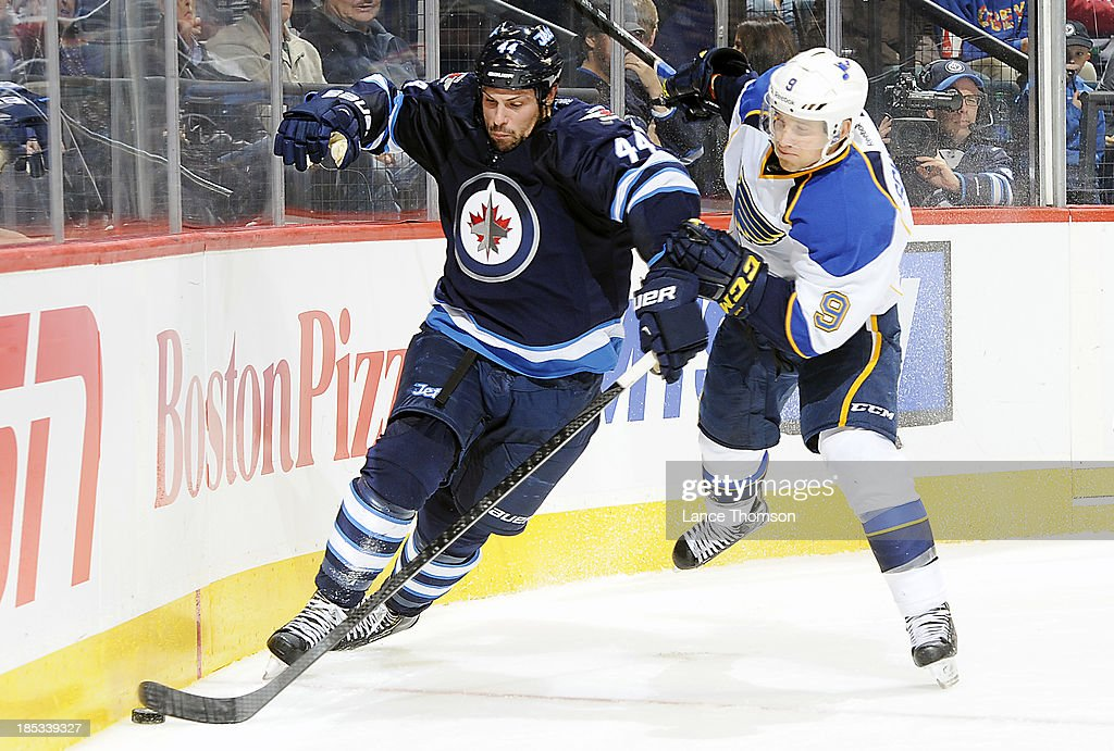 <a gi-track='captionPersonalityLinkClicked' href=/galleries/search?phrase=Zach+Bogosian&family=editorial&specificpeople=4195061 ng-click='$event.stopPropagation()'>Zach Bogosian</a> #44 of the Winnipeg Jets plays the puck along the end boards as <a gi-track='captionPersonalityLinkClicked' href=/galleries/search?phrase=Jaden+Schwartz&family=editorial&specificpeople=7029354 ng-click='$event.stopPropagation()'>Jaden Schwartz</a> #9 of the St. Louis Blues gives chase during third period action at the MTS Centre on October 18, 2013 in Winnipeg, Manitoba, Canada.