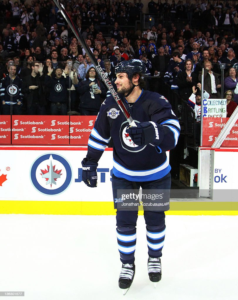 <a gi-track='captionPersonalityLinkClicked' href=/galleries/search?phrase=Zach+Bogosian&family=editorial&specificpeople=4195061 ng-click='$event.stopPropagation()'>Zach Bogosian</a> #4 of the Winnipeg Jets raises his stick as he salutes the fans following a 3-2 victory over the Toronto Maple Leafs at the MTS Centre on December 31, 2011 in Winnipeg, Manitoba, Canada.