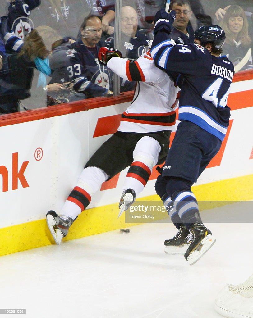 Zach Bogosian #44 of the Winnipeg Jets rubs out Mark Fayne #29 of the New Jersey Devils along the end boards during second period action at the MTS Centre on February 28, 2013 in Winnipeg, Manitoba, Canada.