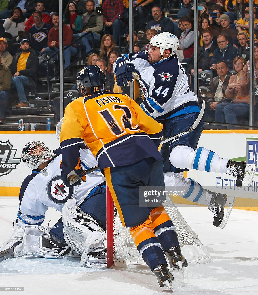 Zach Bogosian #44 of the Winnipeg Jets swipes at the puck above Jets goalie Ondrej Pavelec #31 during action against Mike Fisher #12 of the Nashville Predators at Bridgestone Arena on October 24, 2013 in Nashville, Tennessee.