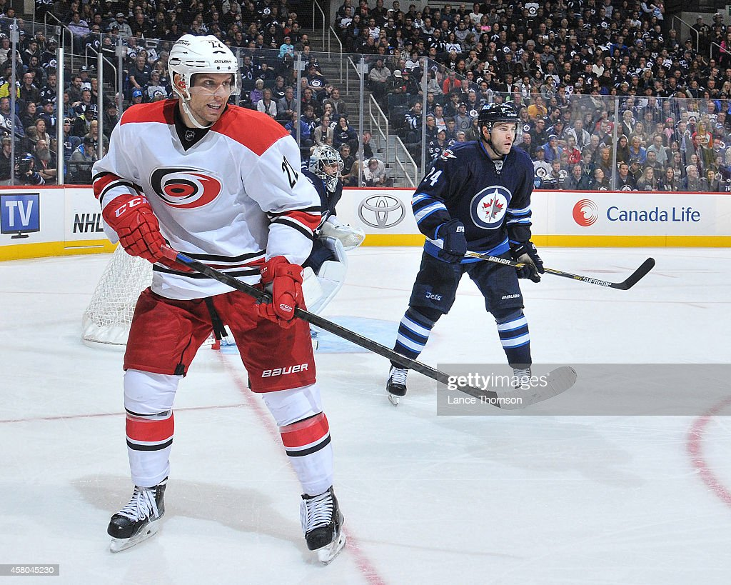 Zach Boychuk of the Carolina Hurricanes and Grant Clitsome of the Winnipeg Jets keep an eye on the play along the boards during third period action...