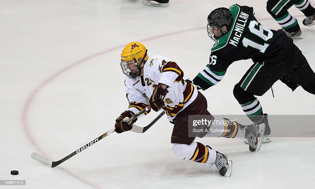 Zach Budish #24 of Minnesota is tripped by Mark MacMillan #16 of North Dakota January 19, 2013 at Mariucci Arena in Minneapolis, Minnesota.