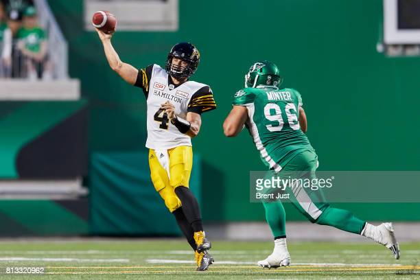 Zach Collaros of the Hamilton Tiger Cats throws before the rush of Zach Minter of the Saskatchewan Roughriders can reach him in the game between the...