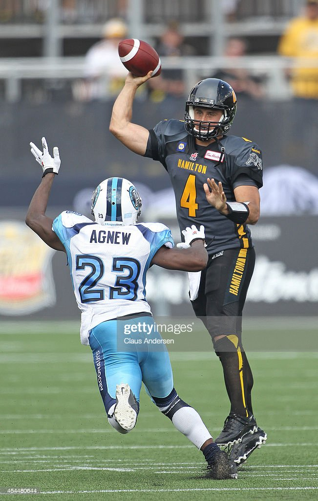 <a gi-track='captionPersonalityLinkClicked' href=/galleries/search?phrase=Zach+Collaros&family=editorial&specificpeople=6237743 ng-click='$event.stopPropagation()'>Zach Collaros</a> #4 of the Hamilton Tiger-cats fires a pass over Vincent Agnew #23 of the Toronto Argonauts in a CFL football game at Tim Hortons Field on September 1, 2014 in Hamilton, Ontario, Canada.The Tiger-cats defeated the Argonauts 13-12.