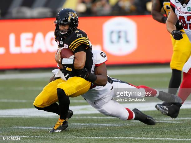 Zach Collaros of the Hamilton TigerCats gets tackled by Avery Ellis of the Ottawa Redblacks during a CFL game at Tim Hortons Field on August 18 2017...