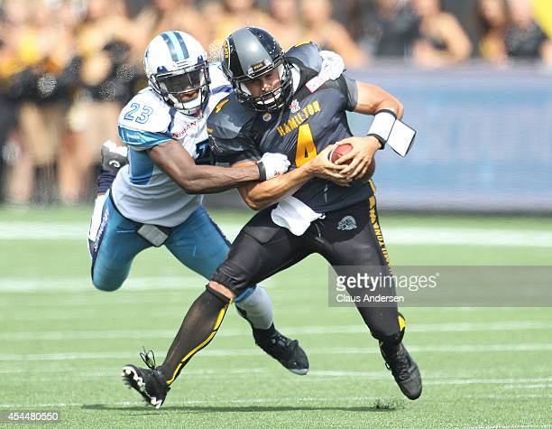 Zach Collaros of the Hamilton Tigercats is brought down by Vincent Agnew of the Toronto Argonauts in a CFL football game at Tim Hortons Field on...