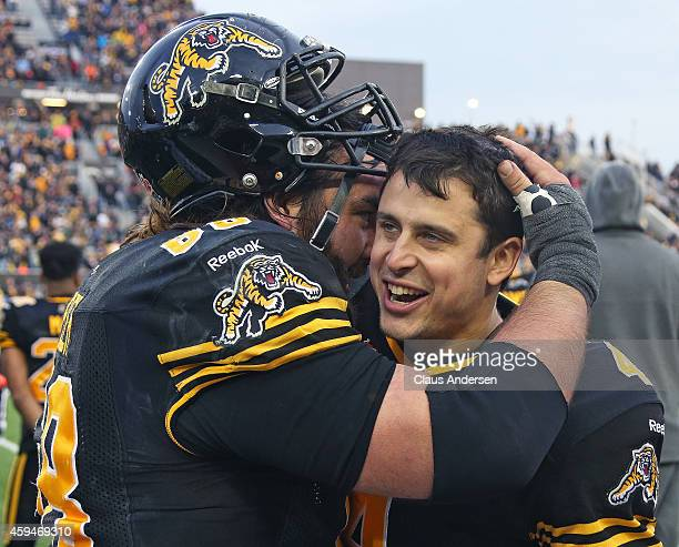 Zach Collaros of the Hamilton TigerCats receives congratulations from teammate Mike Filer after defeating the Montreal Alouettes in the CFL football...