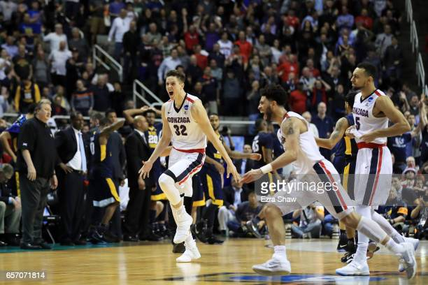 Zach Collins and Josh Perkins celebrate their 61 to 58 win over the West Virginia Mountaineers during the 2017 NCAA Men's Basketball Tournament West...