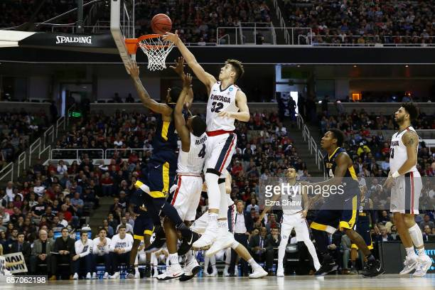 Zach Collins of the Gonzaga Bulldogs blocks a shot by Tarik Phillip of the West Virginia Mountaineers in the first half during the 2017 NCAA Men's...