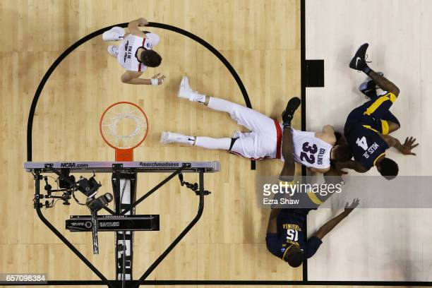 Zach Collins of the Gonzaga Bulldogs fights for a loose ball with Lamont West and Daxter Miles Jr #4 of the West Virginia Mountaineers in the first...