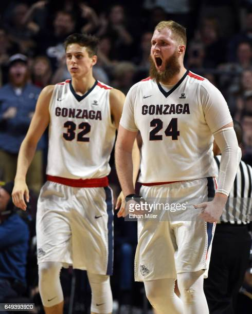 Zach Collins of the Gonzaga Bulldogs looks on as teammate Przemek Karnowski reacts after hitting a shot and getting fouled during the championship...