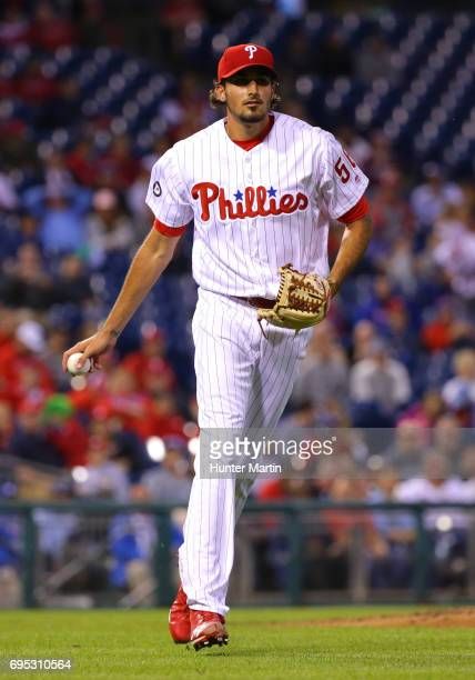 Zach Eflin of the Philadelphia Phillies tosses the ball underhanded to first base during a game against the Colorado Rockies at Citizens Bank Park on...