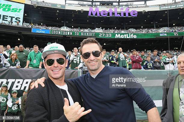 Zach Efron and Hugh Jackman strike a pose when they attend the New York Jets versus Seattle Seahawks game at MetLife Stadium on October 2 2016 in...