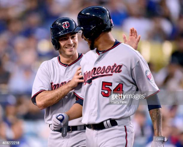 Zach Granite and Ervin Santana of the Minnesota Twins celebrate their runs from a Joe Mauer single to take a 30 lead over the Los Angeles Dodgers...
