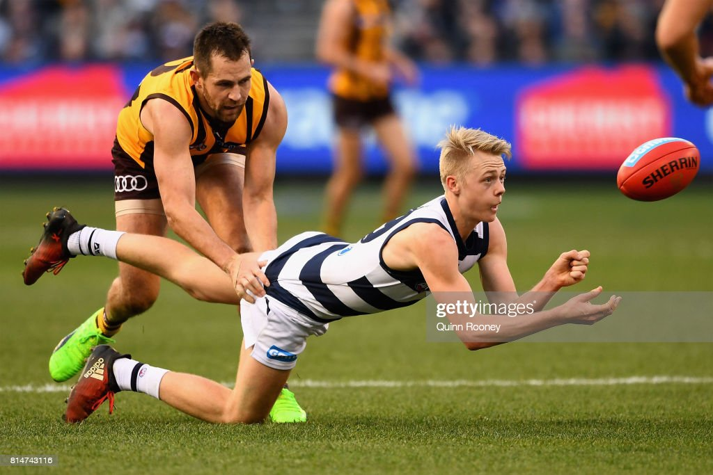 Zach Guthrie of the Cats handballs whilst being tackled by Luke Hodge of the Hawks during the round 17 AFL match between the Geelong Cats and the Hawthorn Hawks at Melbourne Cricket Ground on July 15, 2017 in Melbourne, Australia.
