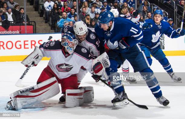 Zach Hyman of the Toronto Maple Leafs and Scott Harrington of the Columbus Blue Jackets battle in front of Joonas Korpisalo of the Columbus Blue...