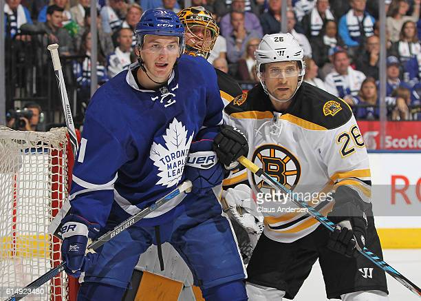 Zach Hyman of the Toronto Maple Leafs battles against JohnMichael Liles of the Boston Bruins during an NHL game on October 15 2016 at the Air Canada...