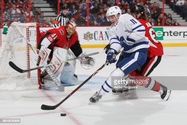 Zach Hyman of the Toronto Maple Leafs controls the puck deep in the offensive zone against Erik Karlsson and Craig Anderson of the Ottawa Senators at...