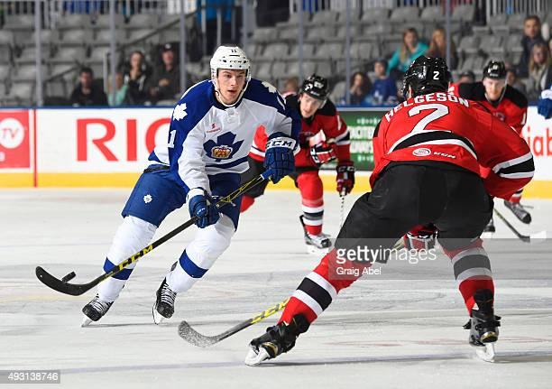 Zach Hyman of the Toronto Marlies controls the puck around Seth Helgeson of the Albany Devils during game action on October 17 2015 at the Ricoh...