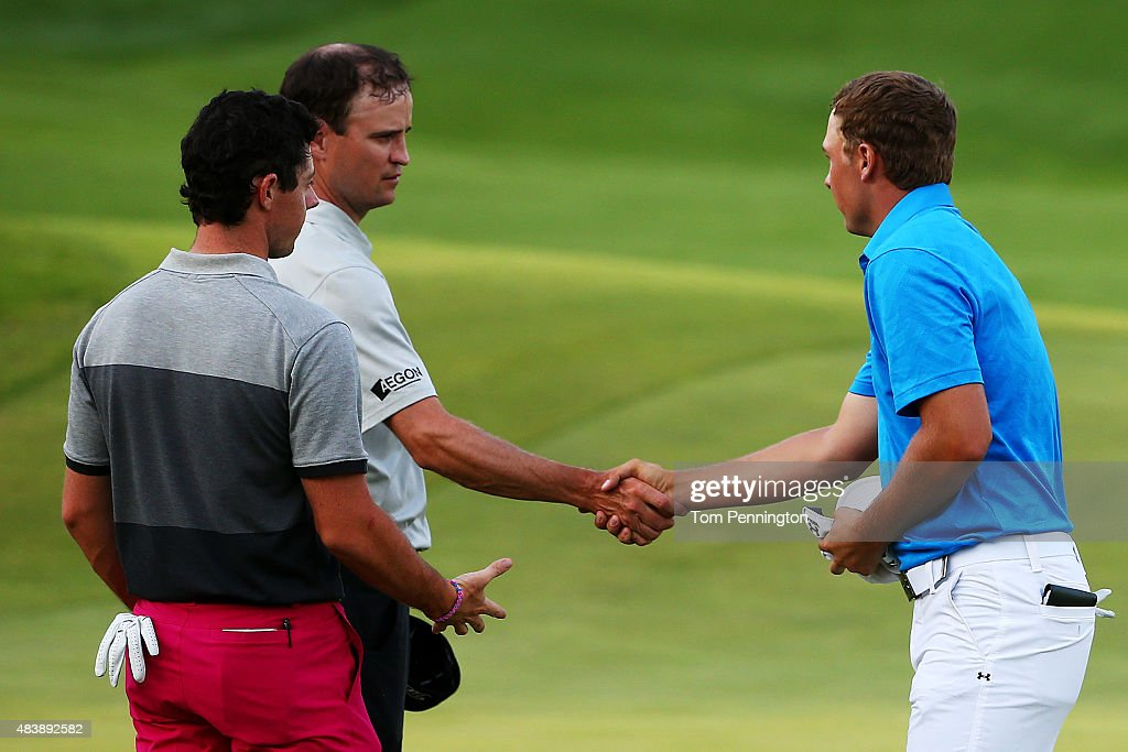 Zach Johnson and Jordan Spieth of the United States shake hands as Rory McIlroy of Northern Ireland looks on after finishing their first round of the 2015 PGA Championship at Whistling Straits on August 13, 2015 in Sheboygan, Wisconsin.