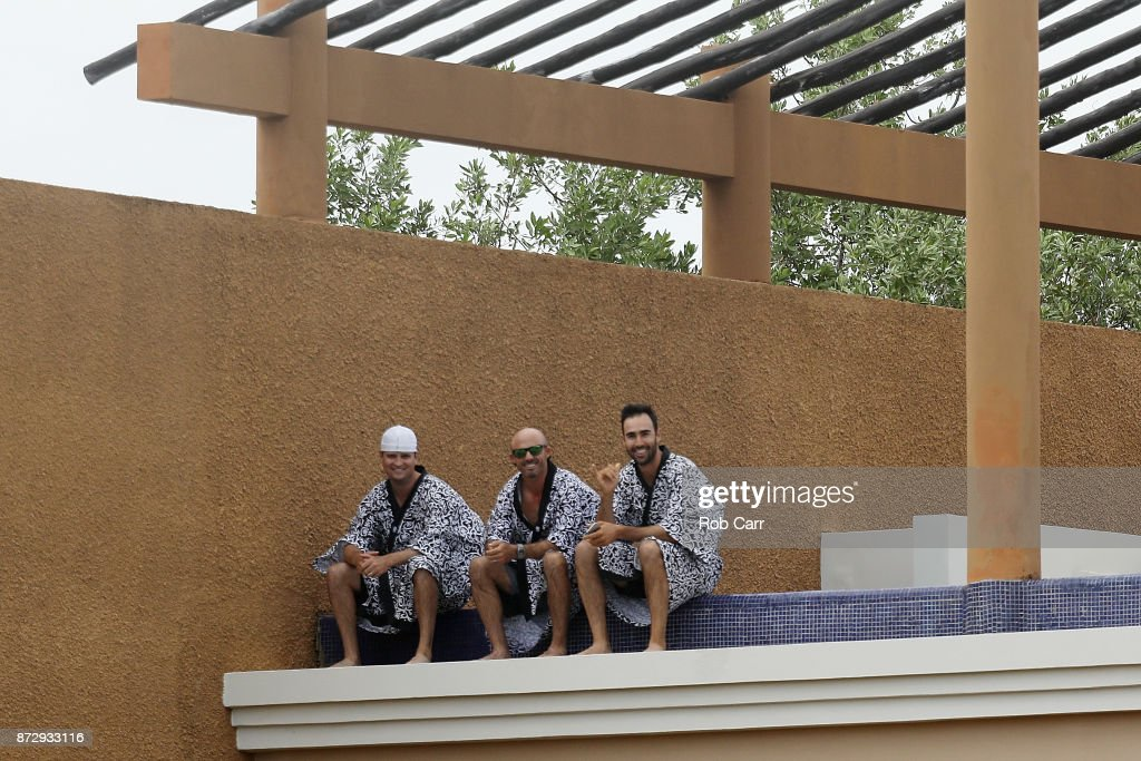 Zach Johnson of the United States, Jonathan Byrd of the United States and Cameron Tringale of the United States look on in bath robes from a balcony during the continuation of the second round of the OHL Classic at Mayakoba on November 11, 2017 in Playa del Carmen, Mexico.