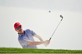 Zach Johnson of the United States team plays a bunker shot during a practice round prior to the start of The Presidents Cup at the Jack Nicklaus Golf...