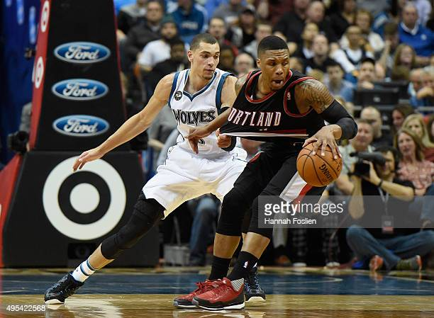 Zach LaVine of the Minnesota Timberwolves guards against Damian Lillard of the Portland Trail Blazers during the third quarter of the home opening...