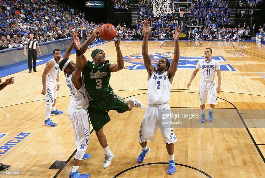 Zach LeDay #3 of the USF Bulls shoots between David Pellom #12 and Shaq Goodwin #2 of the Memphis Tigers on January 26, 2014 at FedExForum in Memphis, Tennessee. Memphis beat South Florida 80-58.