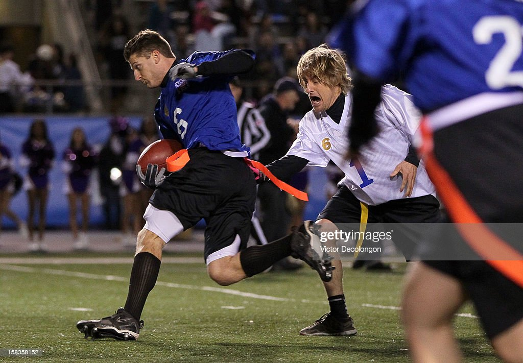 Zach McCall of Team Liberty runs past actor Owen Wilson of Team Freedom during the Got Your 6 And Pat Tillman Foundation Benefit game on December 13, 2012 in Norwalk, California.