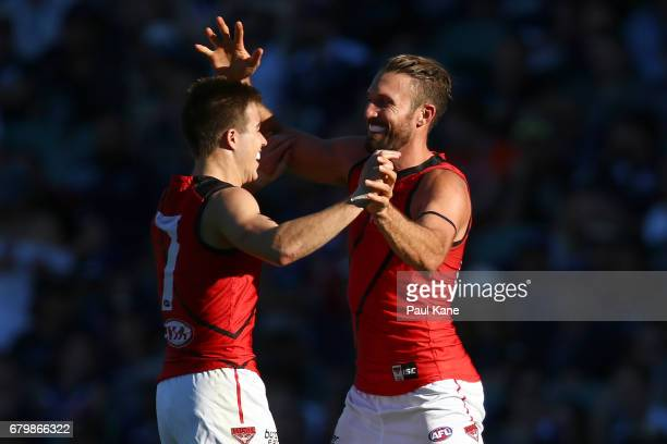 Zach Merrett and Cale Hooker of the Bombers celebrate a goal during the round seven AFL match between the Fremantle Dockers and the Essendon Bombers...