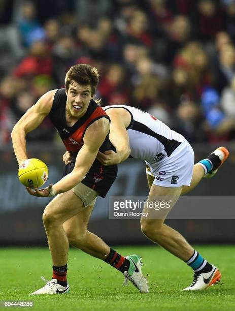Zach Merrett of the Bombers handballs whilst being tackled during the round 12 AFL match between the Essendon Bombers and the Port Adelaide Power at...