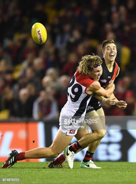 Zach Merrett of the Bombers handballs whilst being tackled Jayden Hunt of the Demons during the round six AFL match between the Essendon Bombers and...