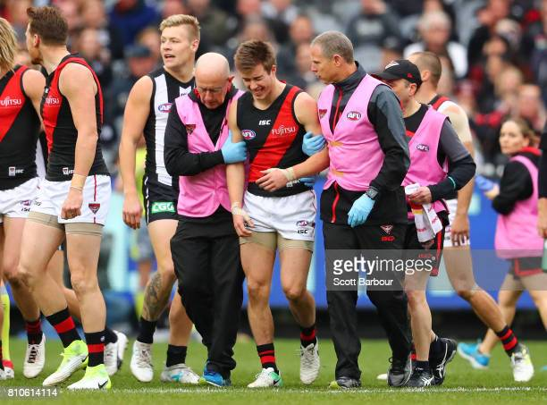Zach Merrett of the Bombers leaves the field injured after a high hit by Levi Greenwood of the Magpies during the round 16 AFL match between the...