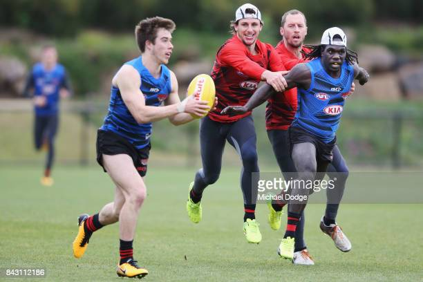 Zach Merrett of the Bombers looks upfield as Anthony McDonaldTipungwuti of the Bombers shepherds away Mark Baguley of the Bombers during an Essendon...