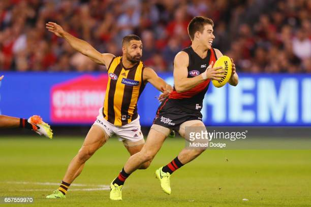 Zach Merrett of the Bombers runs with the ball away from Paul Puopolo of the Hawks during the round one AFL match between the Essendon Bombers and...