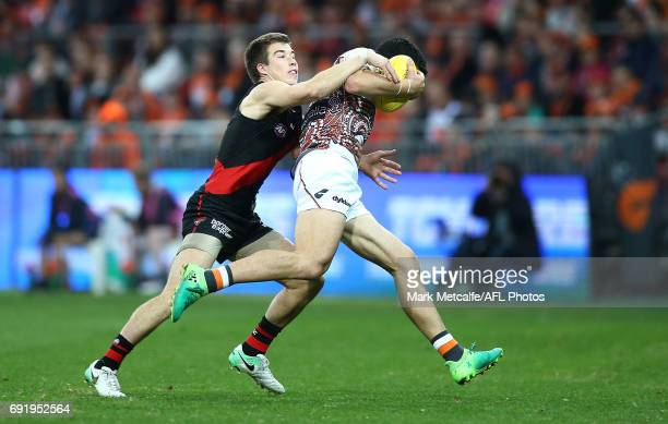 Zach Merrett of the Bombers tackles Matthew Kennedy of the Giants during the round 11 AFL match between the Greater Western Sydney Giants and the...