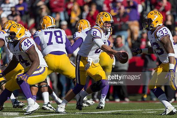 Zach Mettenberger of the LSU Tigers drops back to make a handoff during a game against the Arkansas Razorbacks at Razorback Stadium on November 23...