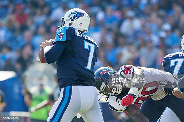 Zach Mettenberger of the Tennessee Titans tries to avoid the rush of Jadeveon Clowney of the Houston Texans at LP Field on October 26 2014 in...