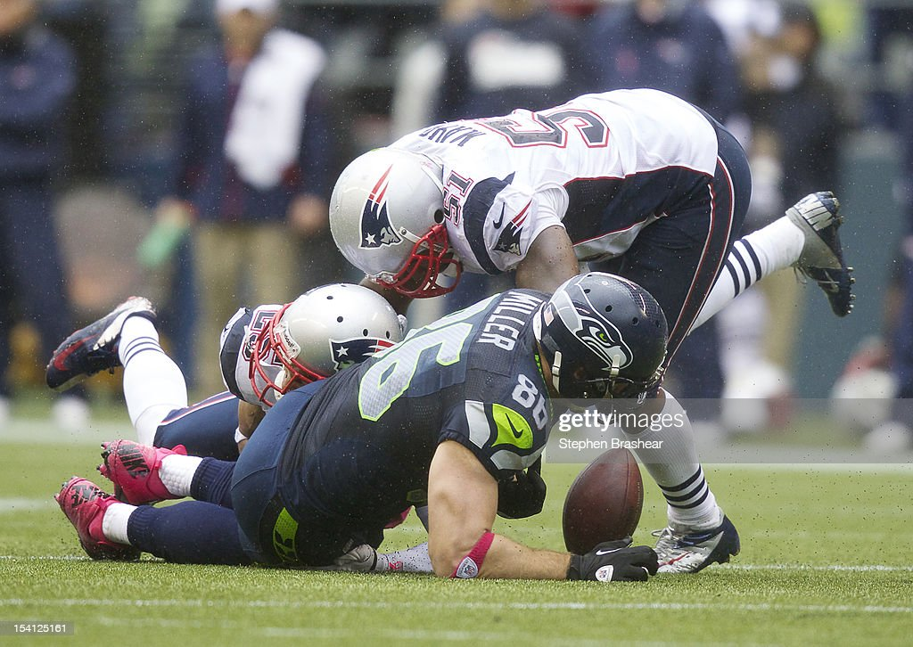 Zach Miller #86 of the Seattle Seahawks fumbles the ball after a hit by Jerod Mayo #51 and Patrick Chung #25 of the New England Patriots during a game at CenturyLink Field on October 14, 2012 in Seattle, Washington. The Seahawks beat the Patriots 24-23.
