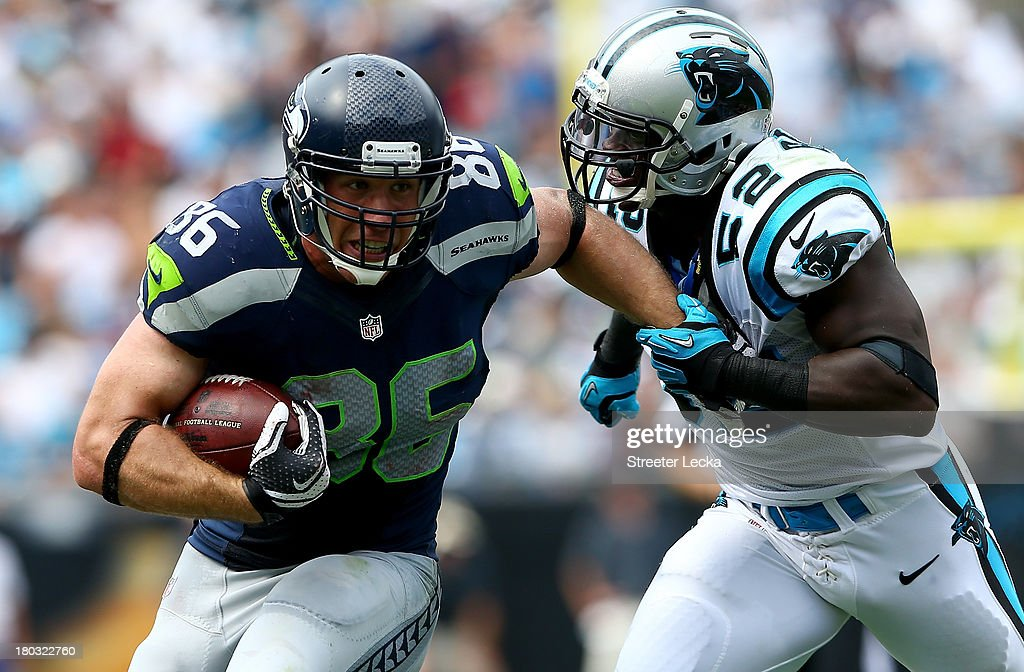 Zach Miller of the Seattle Seahawks runs with the ball as Jon Beason of the Carolina Panthers tries to make a tackle during their game at Bank of...